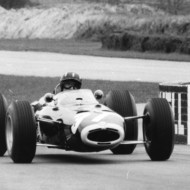 THE RACING LINE (1). Graham Hill threads the needle through the most famous chicane on earth – the only world champion father of a world champion son – Damon. Goodwood 1965